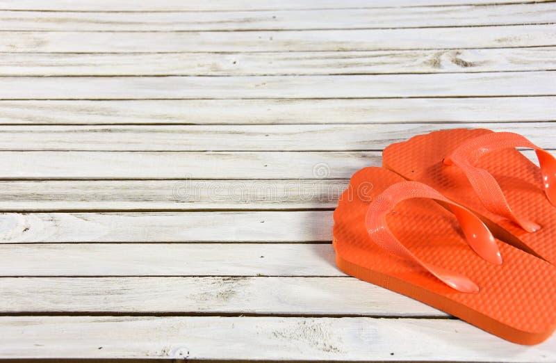 Orange flip-flops on whitewashed wood. Pair of bright orange flip-flops on whitewashed wood decking stock image