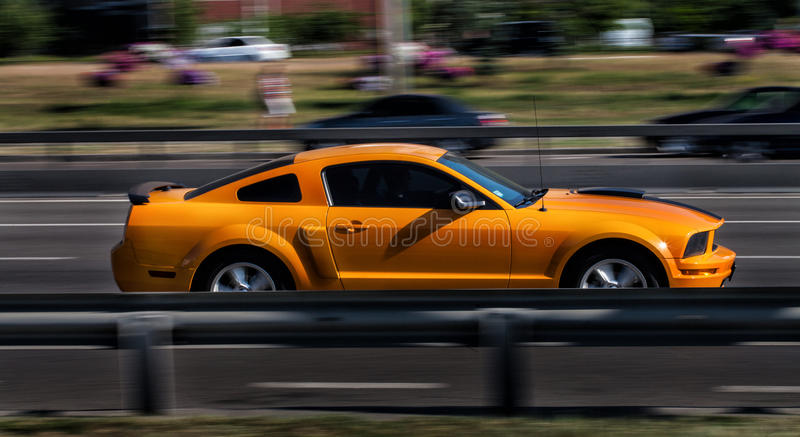 Orange Ford Mustang GT in city stock photography