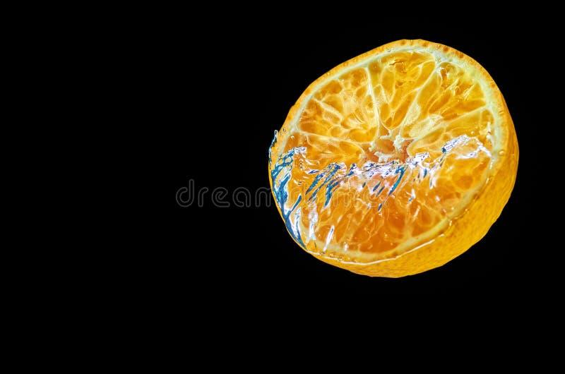 Orange fraîche tombant dans l'eau avec l'éclaboussure sur le fond noir photos stock