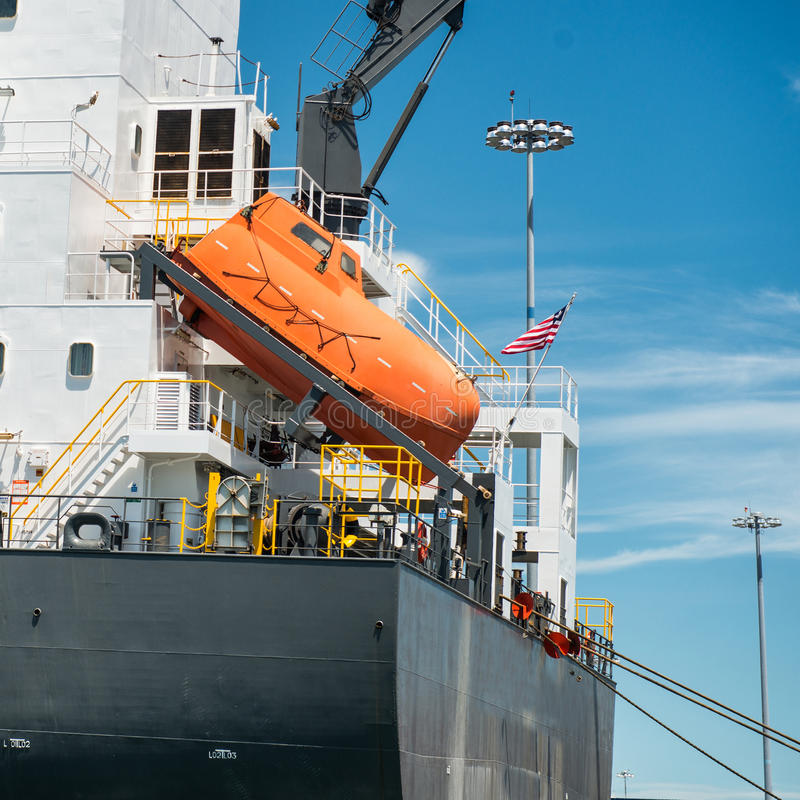 Orange free-fall life boat for emergency crew evacuation installed on cargo ship stock photos