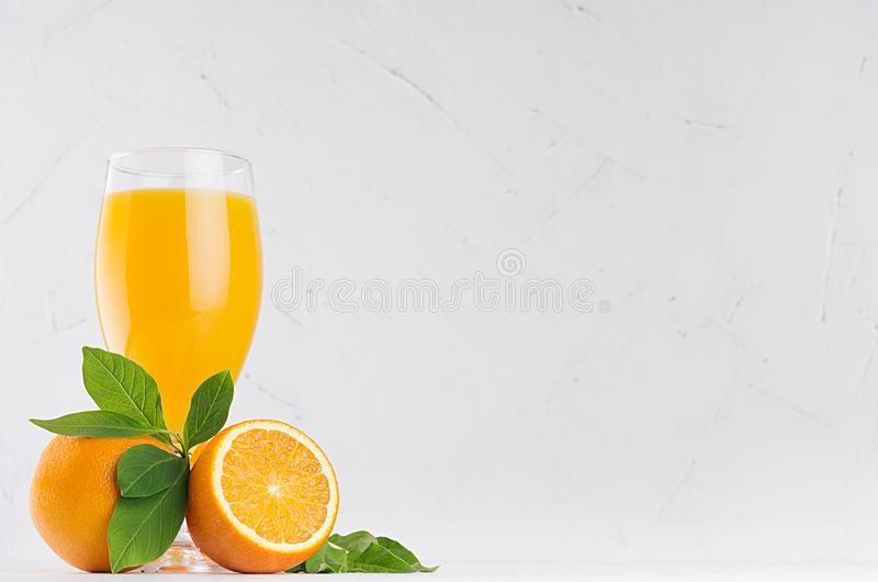 Orange fresh citrus juice with ripe oranges and green leaf on soft white wood board, copy space. Orange fresh citrus juice with ripe oranges and green leaf on royalty free stock photo