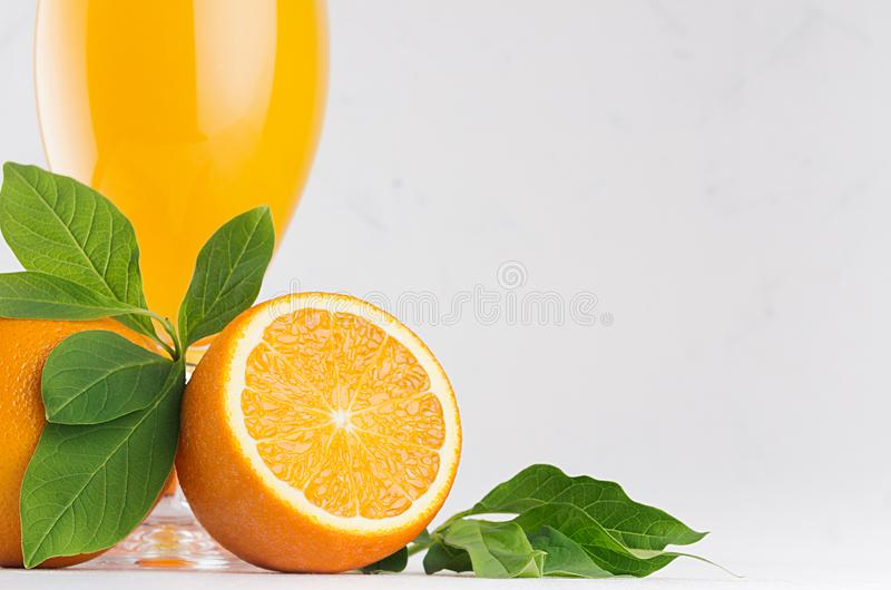 Orange fresh citrus juice with ripe oranges slice macro texture and green leaf on soft white wood board, copy space. Orange fresh citrus juice with ripe oranges stock images