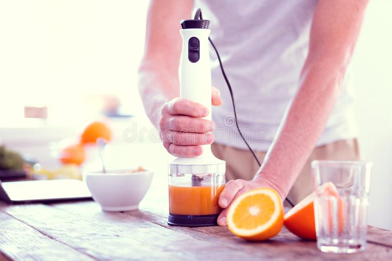 Close up of man using hand blender squeezing orange fresh for early breakfast royalty free stock photo