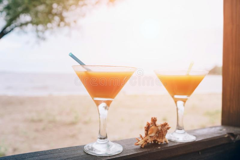 Orange fresh exotic cocktails on wooden edge. Shell lying between glasses. Island life. Paradise. Sun shines bright. Orange fresh exotic cocktails on wooden stock image