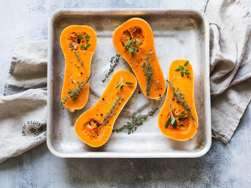 Orange fresh pumpkin cooking with spice and herbs. cut pumpkin slices on a baking sheet. Fresh orange muscat gourd cut in half, re royalty free stock image