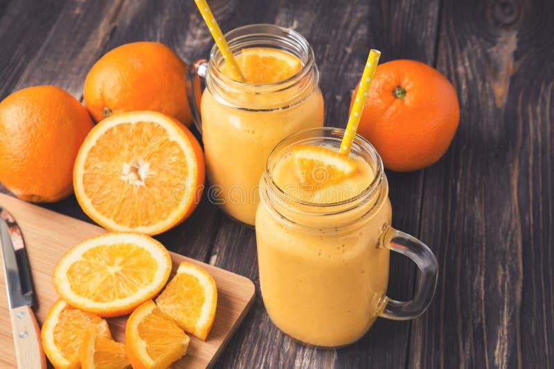 Orange Frucht Smoothie in den Glasgefäßen lizenzfreie stockfotos