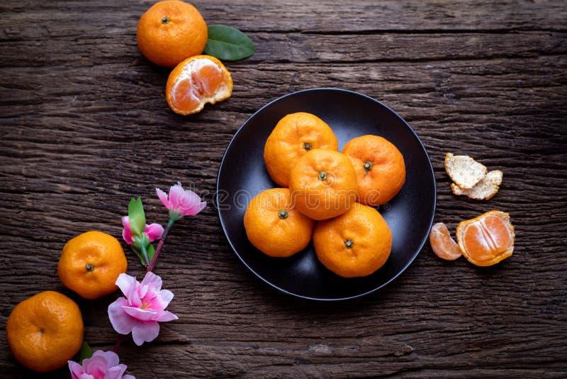 Orange Frucht und rosa Kirschblüte auf hölzerner Tabelle Konzept Festivalhintergrundes des neuen Jahres der Feier des chinesische stockfotos
