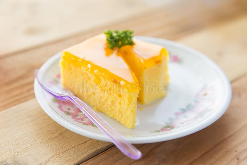 Orange fruit cake on wooden table royalty free stock photography