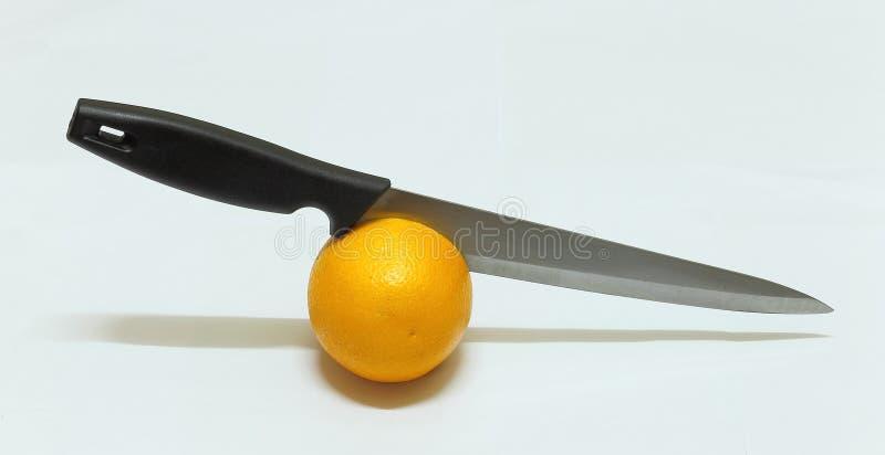 Orange fruit cut by knife. Orange fruit and knife isolated royalty free stock photos
