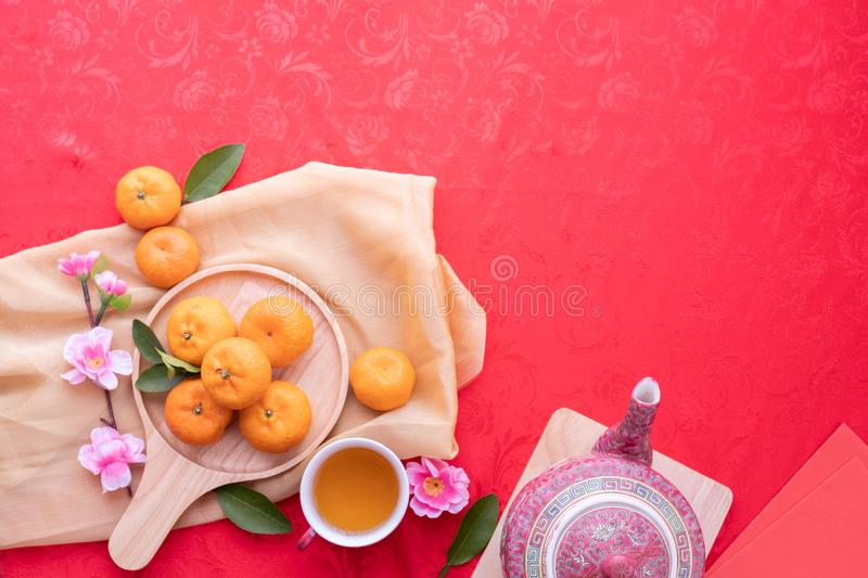 Orange fruit, Pink cherry blossom and teapot with Copy space for text on red texture background, Concept of Chinese new year stock image