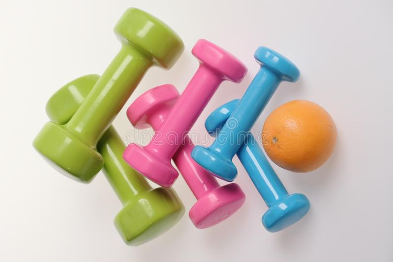 Orange fruit and pink, green and blue barbells making pattern royalty free stock images