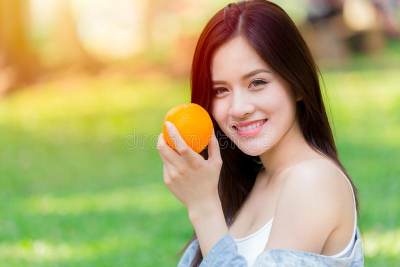 Orange frukt med högt vitamin C för sund asiatisk kvinna royaltyfri bild