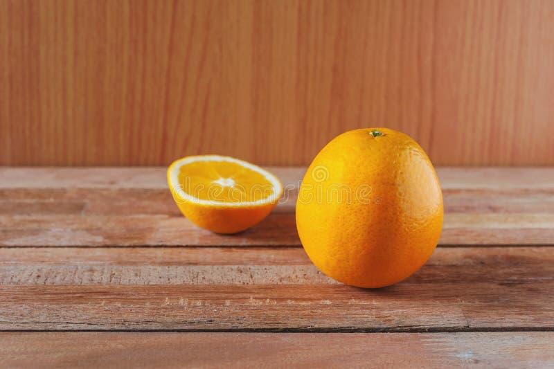 Orange frukt och skiva på trä arkivbilder