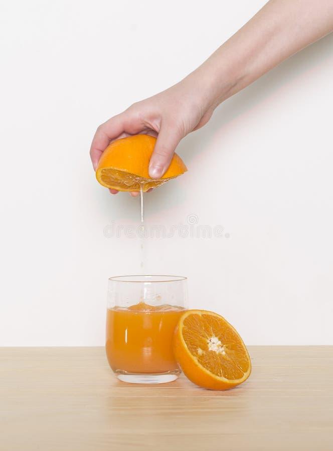 Orange fruktsaft effuse i exponeringsglaset royaltyfria bilder