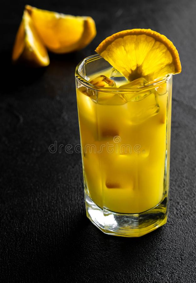 Orange fruktsaft för exponeringsglas med is och skivor som är orange på svart bakgrund arkivbilder