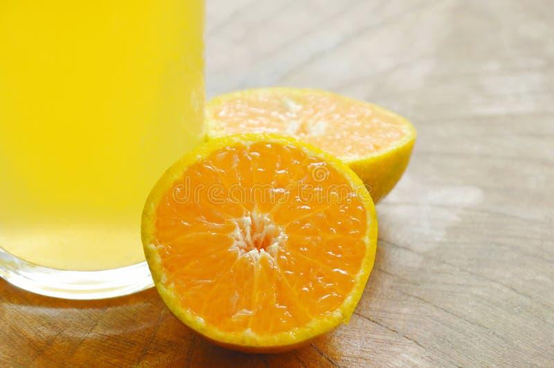 Orange fruktsaft i exponeringsglas- och tangerinklipp på träbräde arkivbild