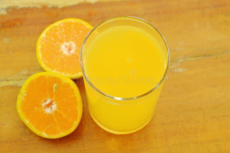 Orange fruktsaft i exponeringsglas- och tangerinklipp på träbräde arkivbilder