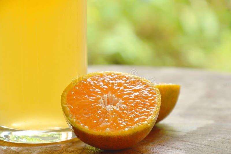 Orange fruktsaft i exponeringsglas- och tangerinklipp på träbräde royaltyfria foton
