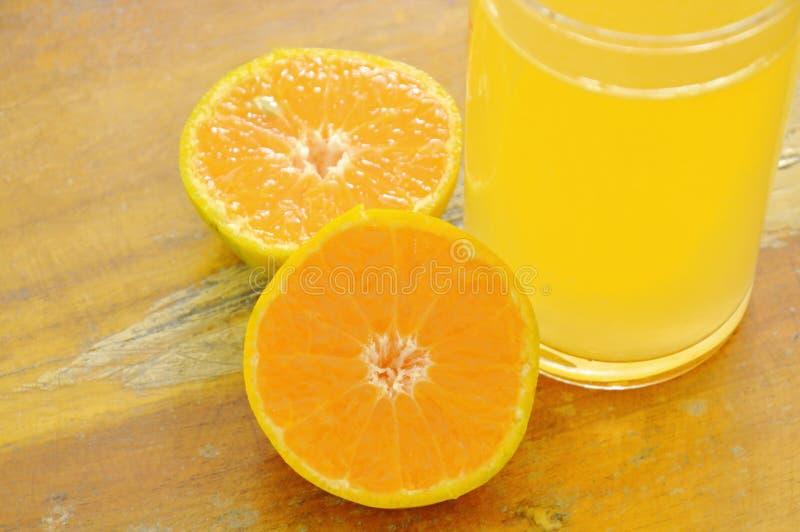 Orange fruktsaft i exponeringsglas- och tangerinklipp på träbräde royaltyfri bild