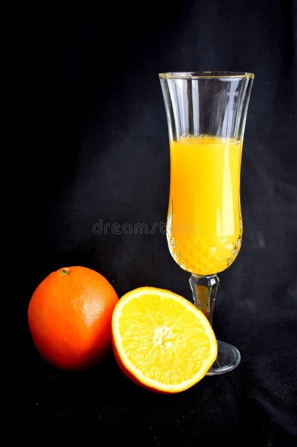 Orange fruktsaft i flöjt med den klippta apelsinen arkivbild