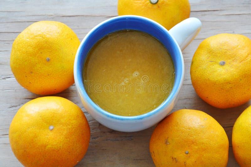 Orange fruktsaft i kopp och tangerin på trätabellen arkivbilder