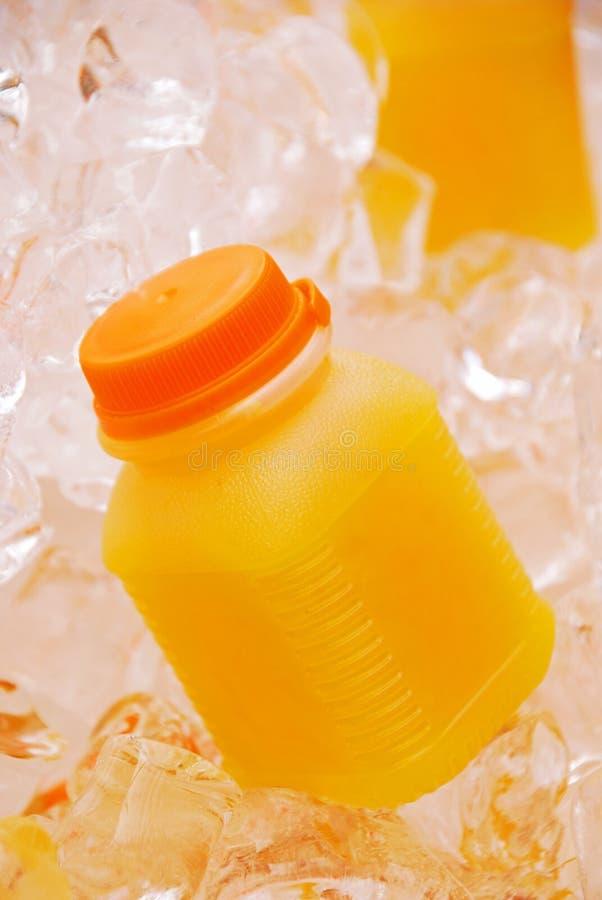 Orange fruktsaft i plast- flaska på iskuber arkivfoto