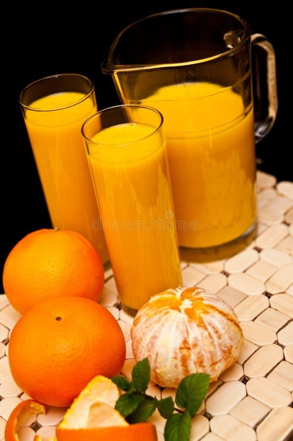 Orange fruktsaft med exponeringsglas royaltyfria foton