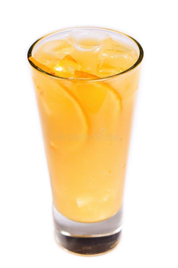 Orange fruktsaft med is och orange stycken i ett exponeringsglas på en isolerad vit bakgrund royaltyfria foton