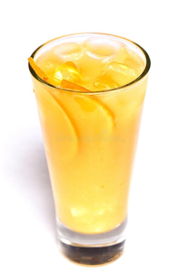 Orange fruktsaft med is och orange stycken i ett exponeringsglas p? en isolerad vit bakgrund arkivfoto