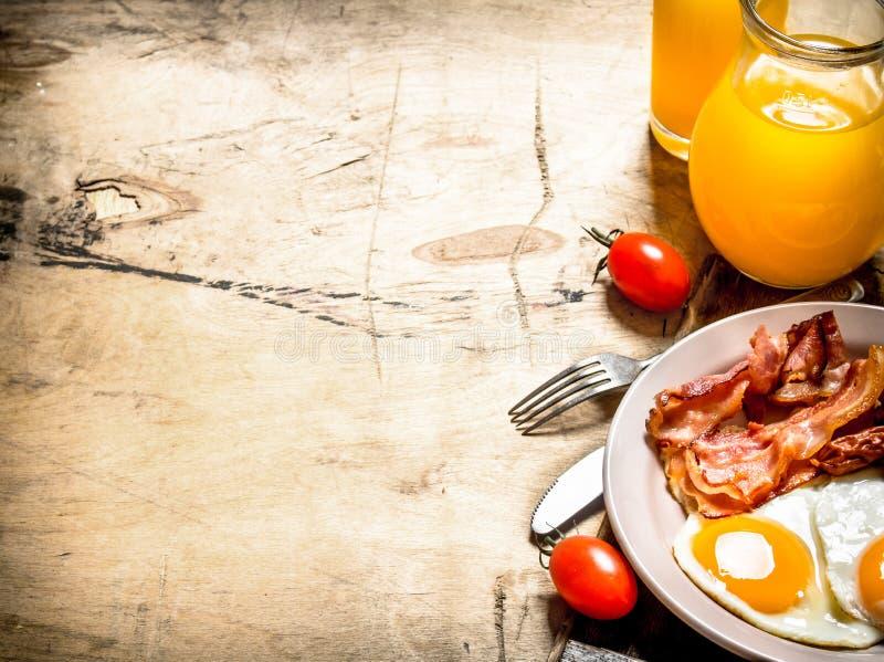 Orange fruktsaft med stekte ägg, bacon och skivor av bröd arkivbild