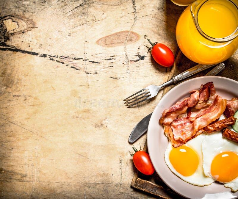 Orange fruktsaft med stekte ägg, bacon och skivor av bröd arkivbilder
