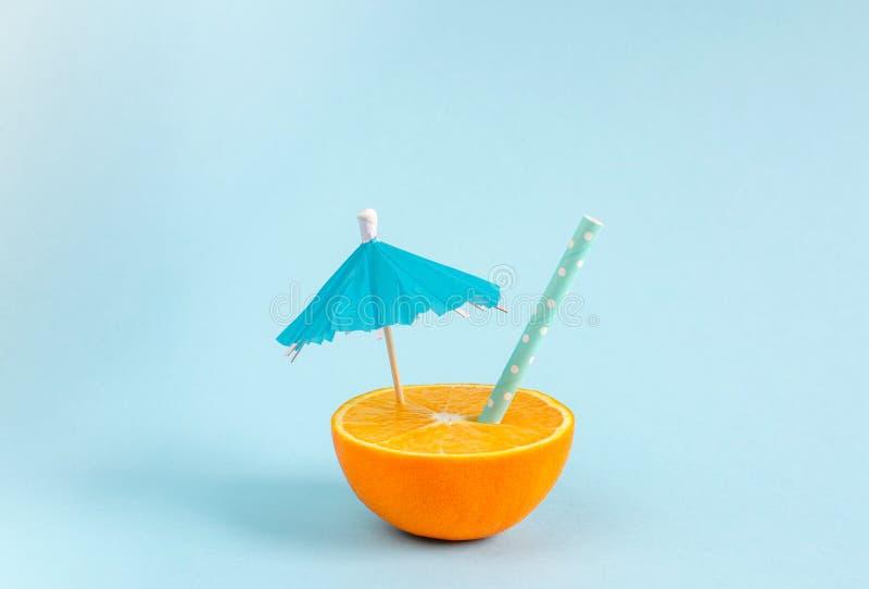 Orange fruktsaft med tubulen och paraplyet Apelsinen klippte i halva p arkivfoton