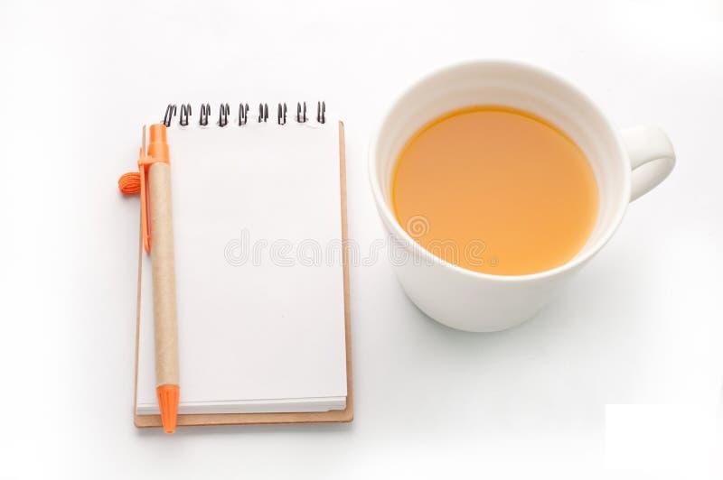 Orange fruktsaft och anteckningsboken skyler över brister på vit bakgrund fotografering för bildbyråer