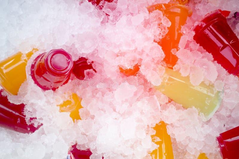 Orange fruktsaft och färgrikt sött vatten på iskristaller fotografering för bildbyråer