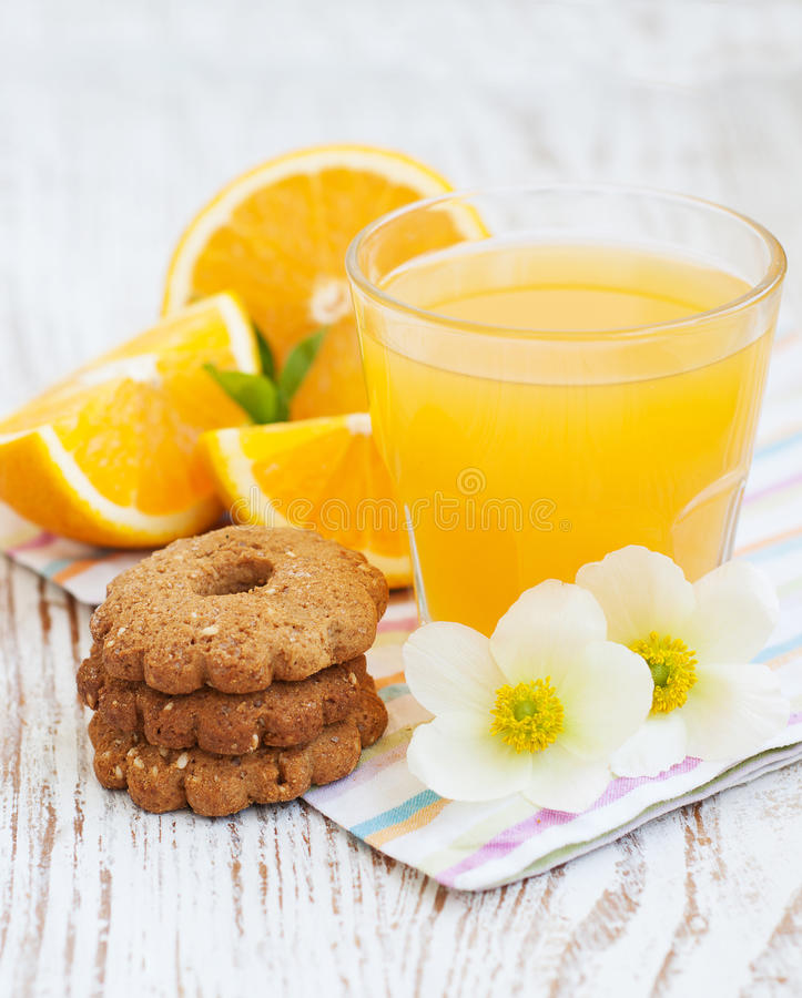 Orange fruktsaft och kakor royaltyfria foton