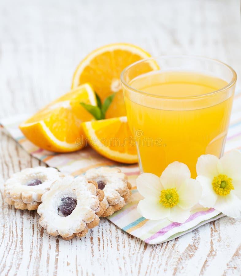 Orange fruktsaft och kakor arkivbild