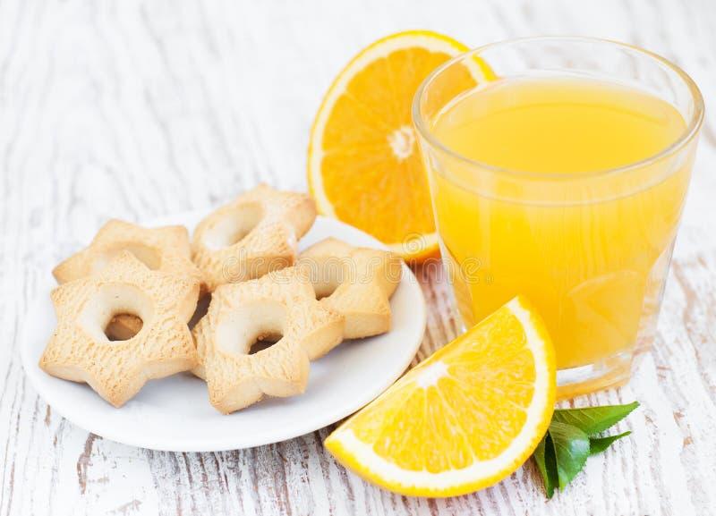 Orange fruktsaft och kakor arkivfoton