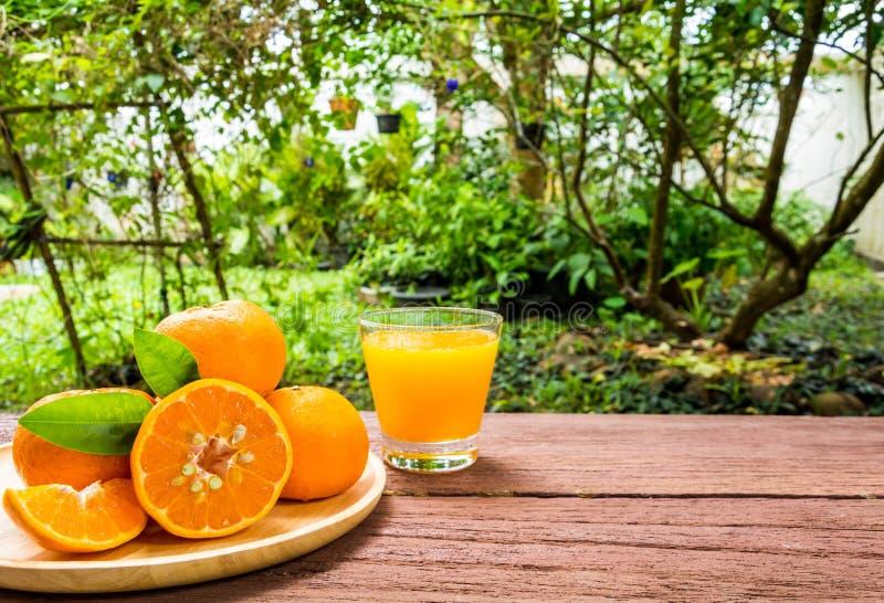 Orange fruktsaft på en trätabell royaltyfri fotografi