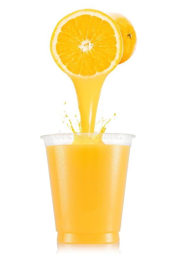 Orange fruktsaft som häller ut från frukt in i den plast- koppen royaltyfria foton