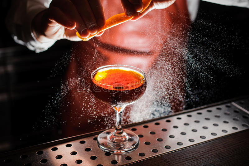 Orange garnish spray over a drink royalty free stock images