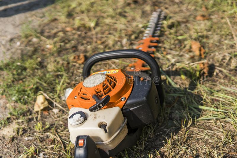 Orange gasoline engine portable chainsaw on a grass. stock photography