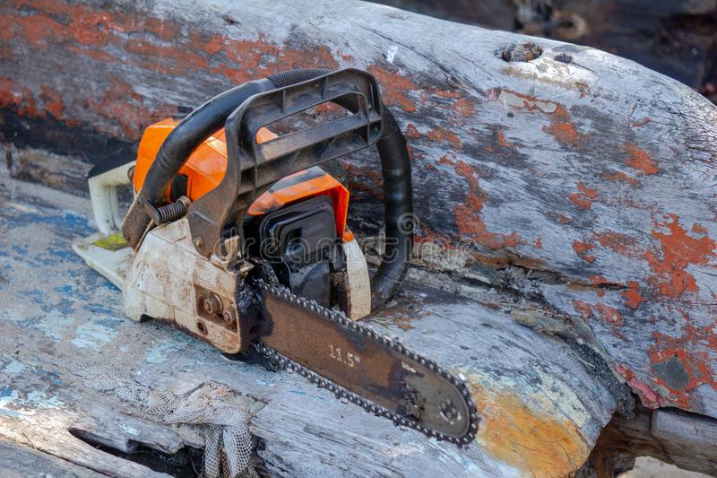 Orange gasoline engine portable chainsaw put on the old wooden plank stock photography