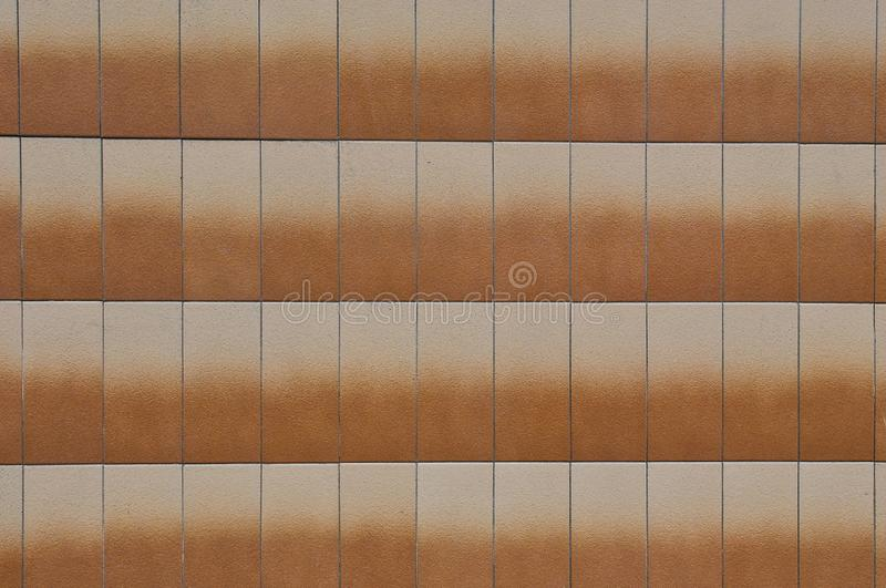 Orange gegen?berstellende Fliesen hergestellt vom Stein auf der Wand des Geb?udes stockfoto