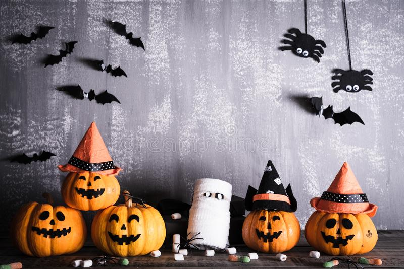 Orange ghost pumpkins with witch hat on gray wooden board background with bat. halloween concept stock image