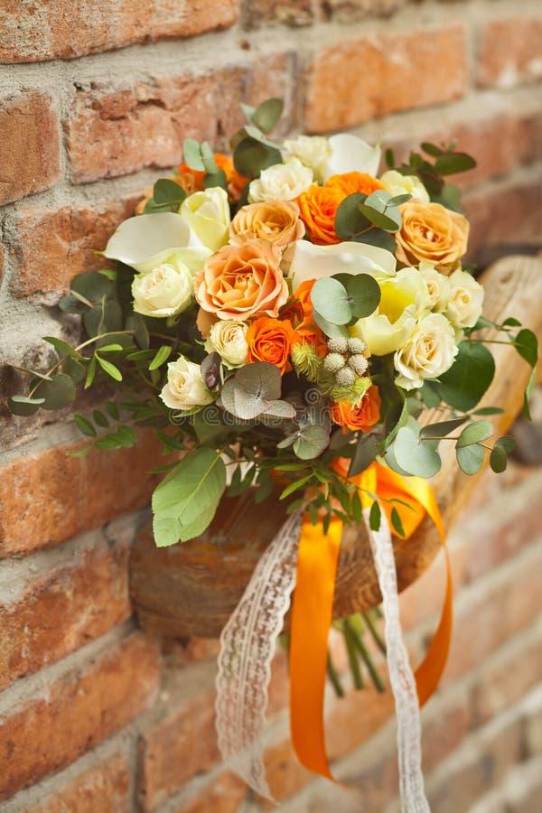 Orange gifta sig bukett på en tegelstenbakgrund arkivfoton