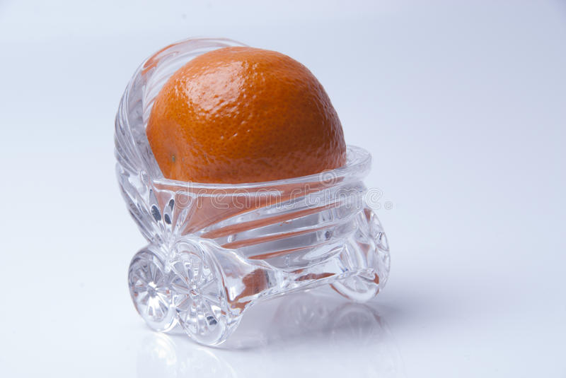Orange in glass bassinet. Small orange in clear glass bassinet stock photos