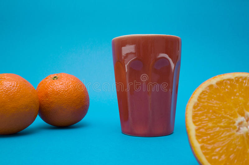 Orange and a glass on blue background stock photos
