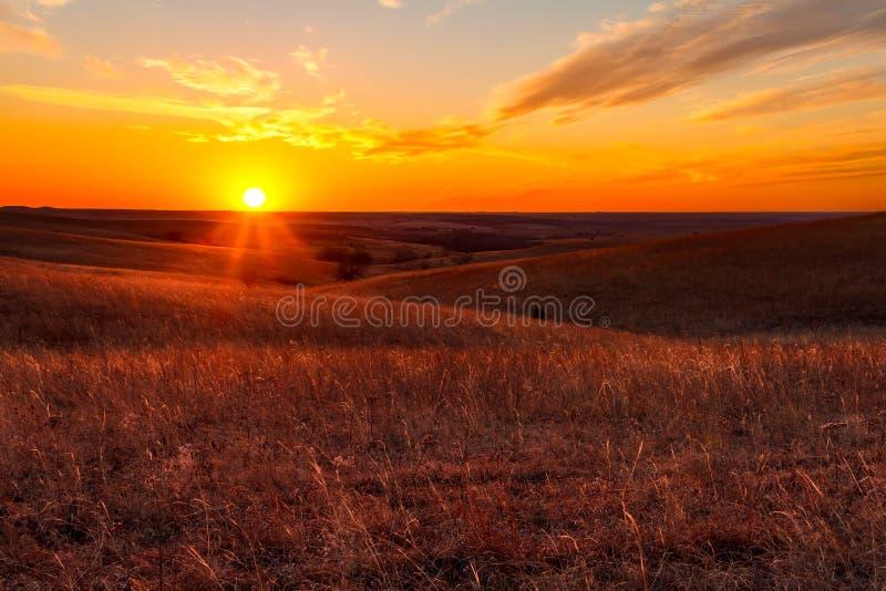 Orange glow of a sunset in Kansas Flint Hills. A view of the sunset in the Flint Hills of Kansas just outside of Alma, Kansas royalty free stock photo
