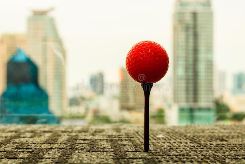 Orange Golfball auf T-Stück hinter Stadtbildszene im Büro Gehen Sie lizenzfreies stockbild