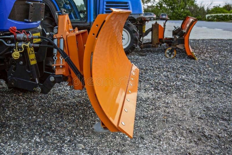 Orange grävarehink för snö två Liten snowblower Utrustning för snöborttagning i förväntan av vintern royaltyfria bilder